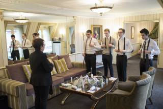 Four first-year students are in a suite of Hotel Napoléon and practice tie knots.