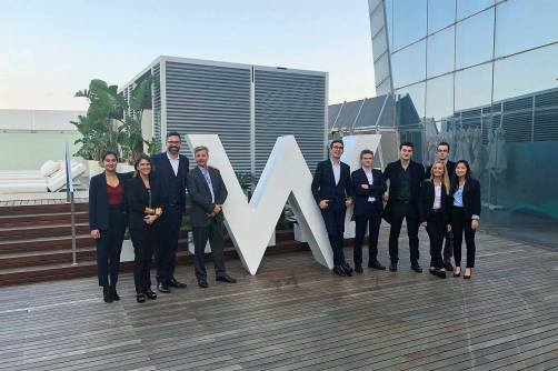 Second-year students spend the day at W hotel in Barcelona. They stand in front of the sign W with their lecturers.