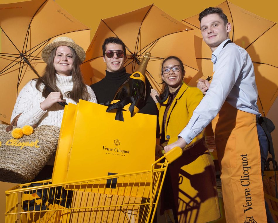 Group photo of students at Veuve Cliquot, covered with objects of this yellow so specific to the famous brand of champagne