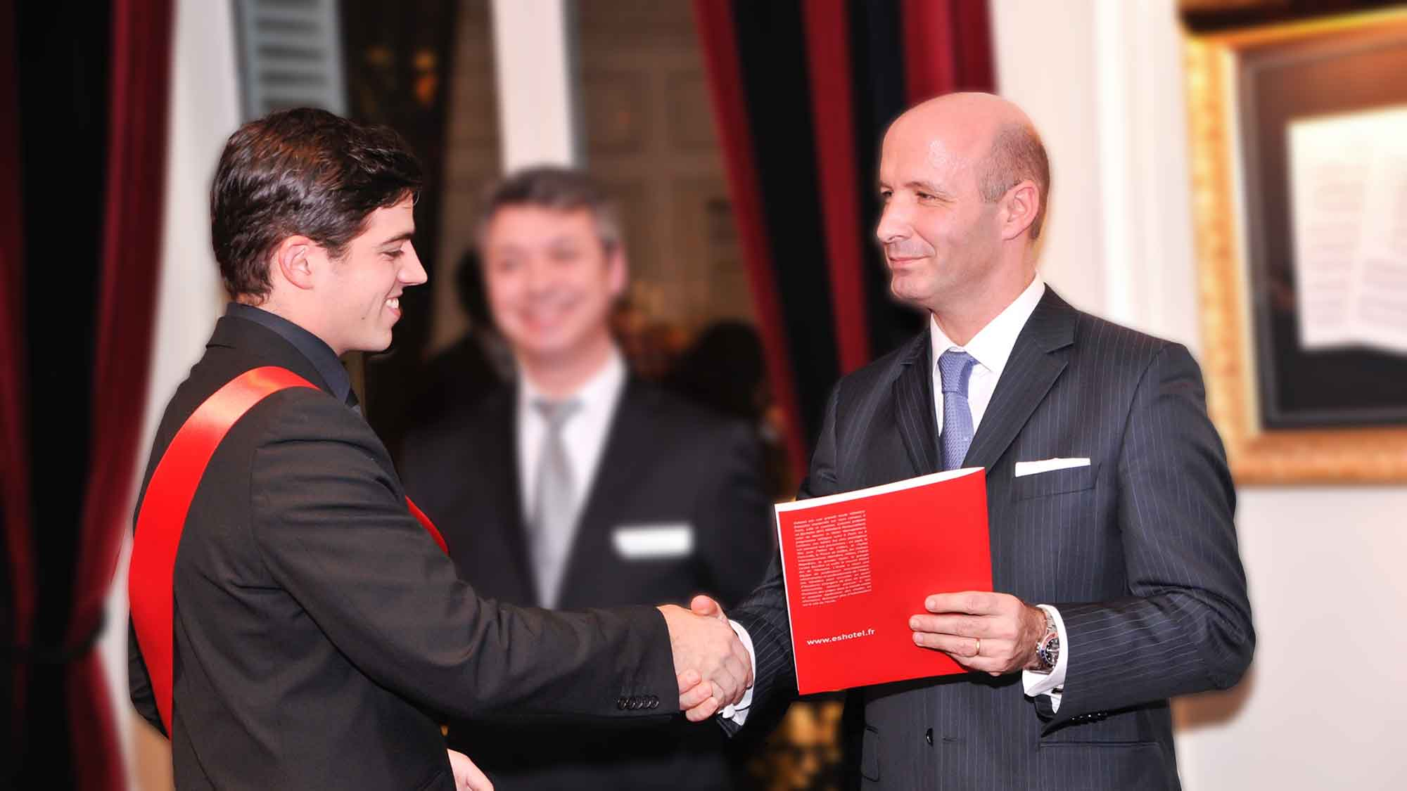 Christophe Laure, General Manager of InterContinental Paris, Le Grand Hotel, shakes hands with a Master's student and is preparing to hand over his degree.