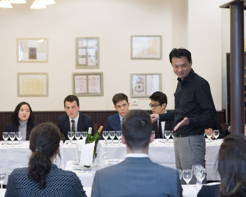 In the restaurant of the Luxury Hotelschool, a lecturer is standing in the middle of seating first year students. They have many glasses in front of them, ready to discover wine and French gastronomy.