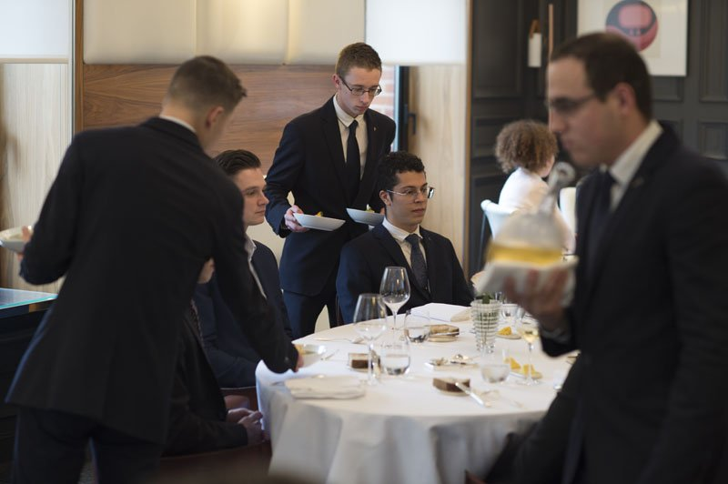 Two young men studying in the top-up Bachelor are seating at the Assiette Champenoise, 3-Michelin-star restaurant.
